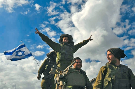 An Israeli soldier gestures from atop an armoured personnel carrier after crossing back into Israel from the Gaza Strip
